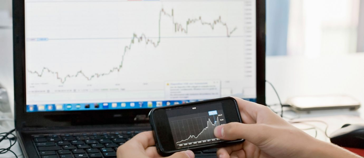 Stock chart on a mobile phone and laptop