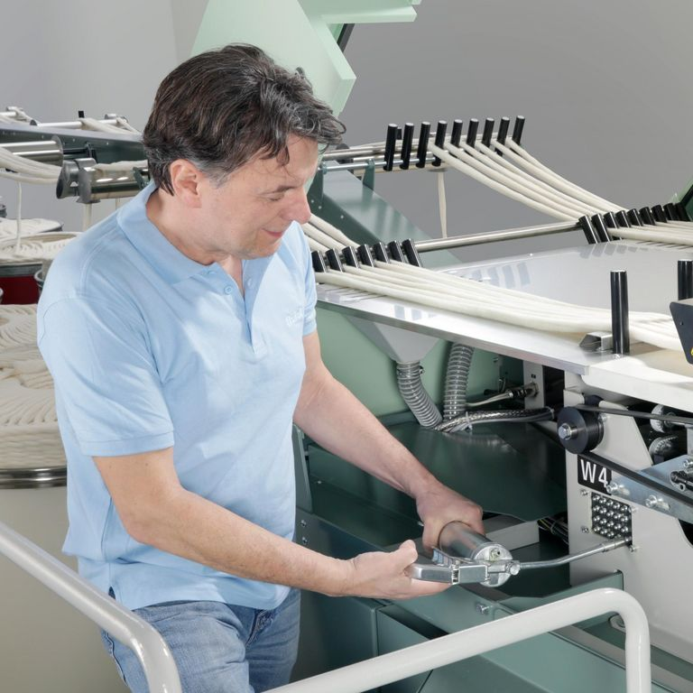Employee working on a Rieter machine